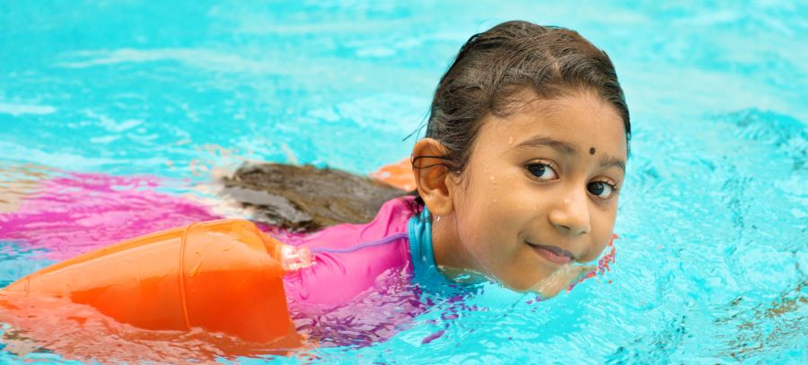 A little girl swimming in a pool wearing floaties