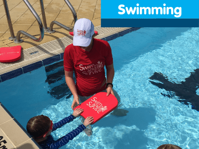A swim instructor in a pool with a child holding a red Swim and Survive kickboard
