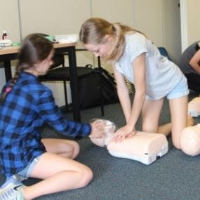 Image of two young girls practising CPR on a manikin